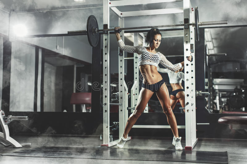 Young fitness brunette girl in the gym posing and relaxing. Young fitness brunette girl in the gym posing and holding the barbell and relaxing on smoke royalty free stock images
