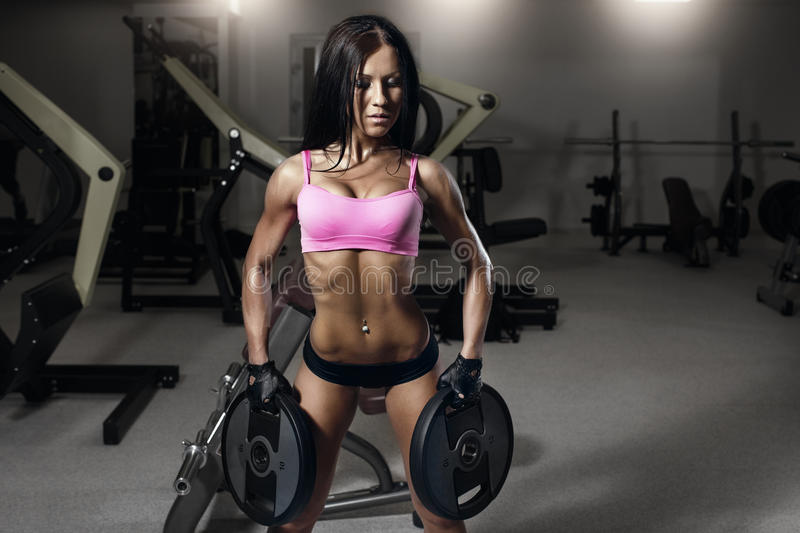 Young fitness brunette woman in the gym doing exercises royalty free stock photo