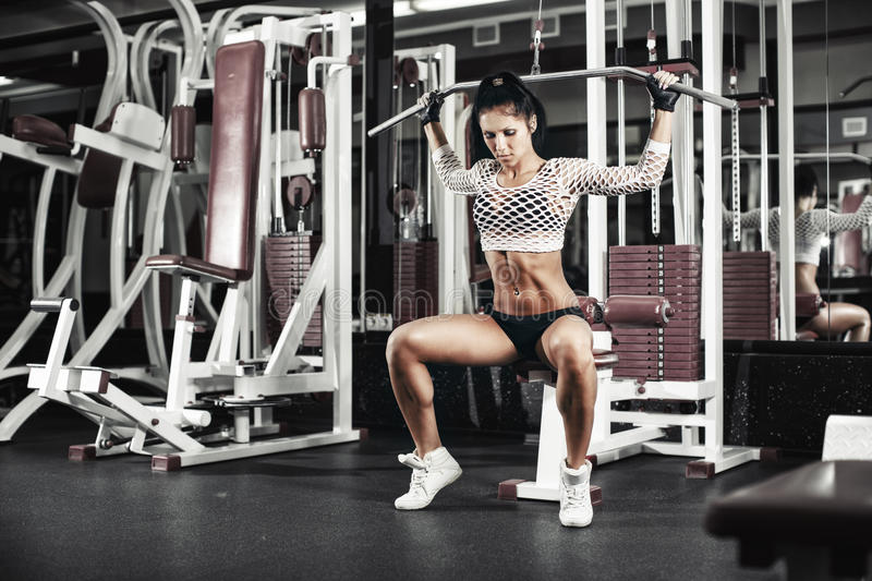 Young fitness girl lifts in the gym in the block simulator stock photography