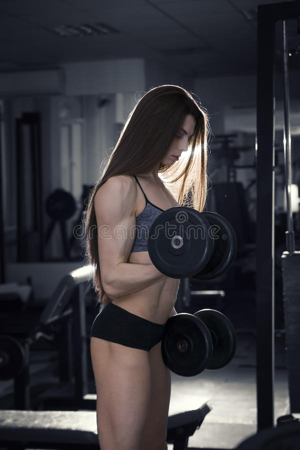 Young fitness girl workout with dumbbells in the gym, woman with perfect muscular body. Black and white background royalty free stock photography