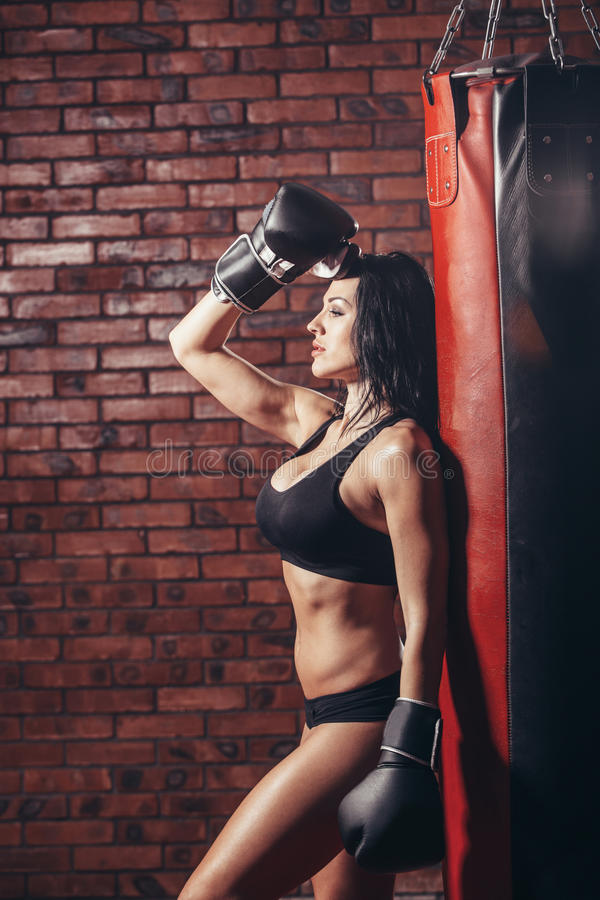 Young girl with boxing gloves, punching bag royalty free stock photo