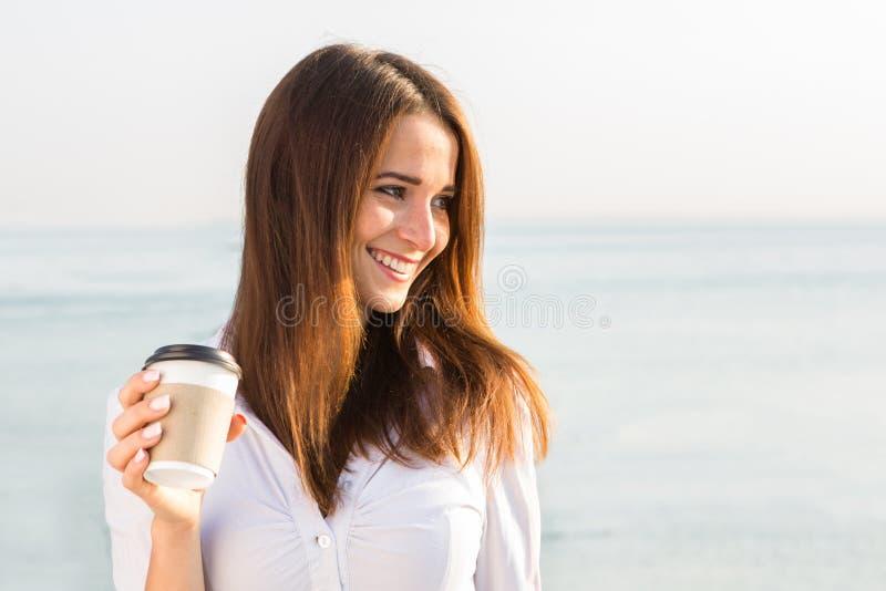 Young girl drinking coffee on seaside stock photo