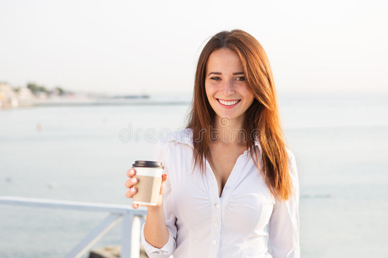Young girl drinking coffee on seaside royalty free stock images