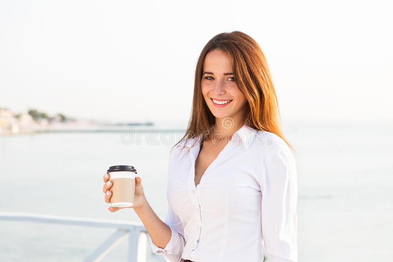 Young girl drinking coffee on seaside royalty free stock image