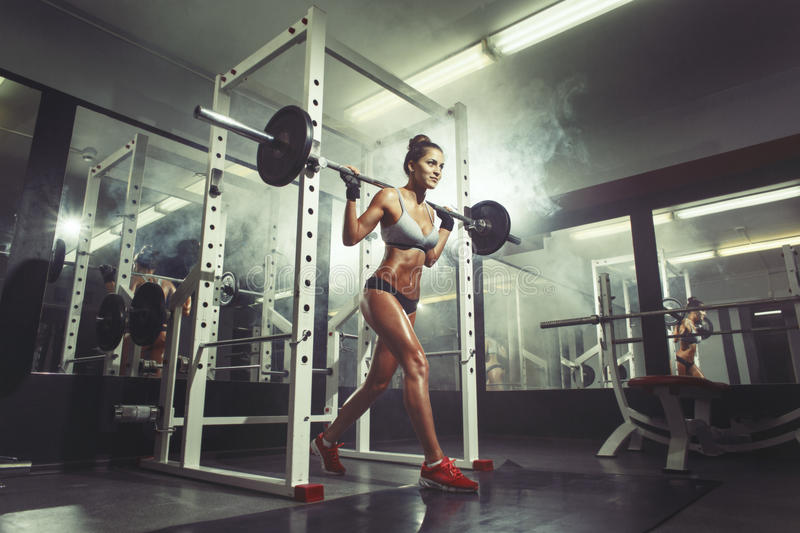 Young girl in the gym doing squat. Young fitness girl in the gym doing squat on smoke background royalty free stock image