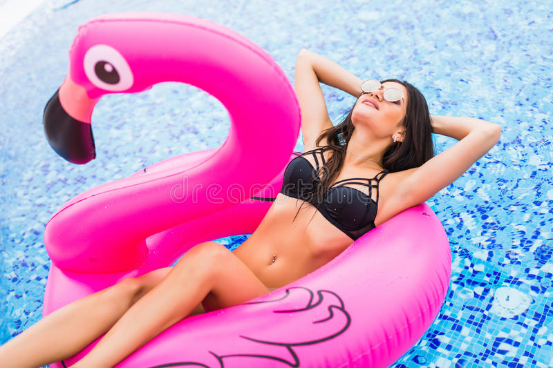 Young and girl having fun and laughing on an inflatable giant pink flamingo pool float mattress in a bikini. Attractive tanne. Young and girl having fun and stock images
