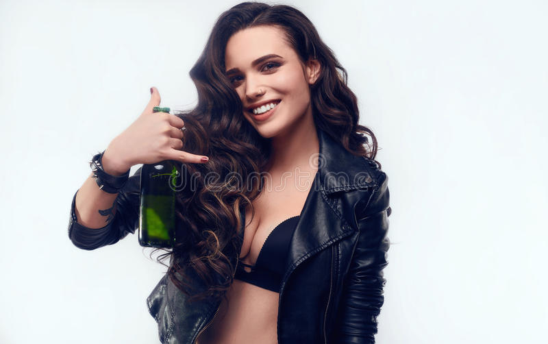 Young girl with long hair in leather jacket with beer. Portrait of young girl with long hair in leather jacket holding bottle of beer isolated on white royalty free stock photo