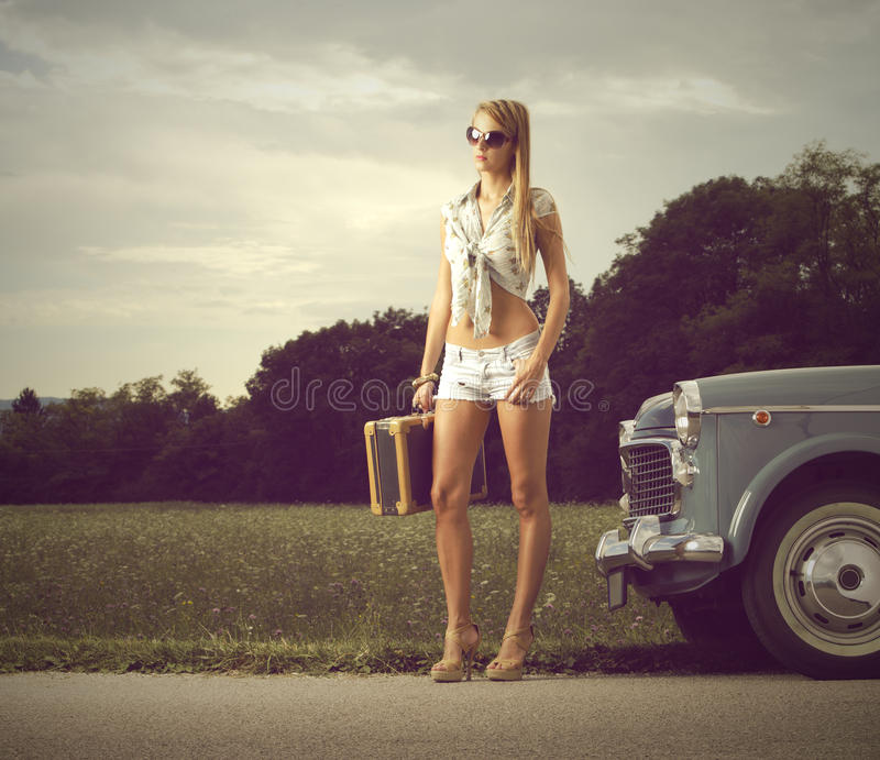 Young girl on the road. Young girl with suitcase and vintage cars royalty free stock photo
