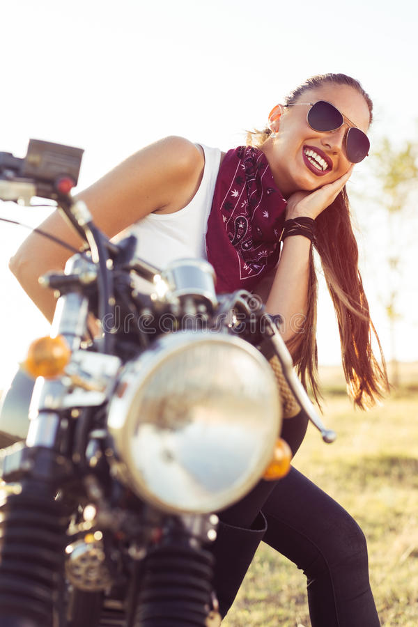 Young girl sitting on vintage custom motorcycle and drinking juice . Outdoor lifestyle portrait. Young girl sitting on vintage custom motorcycle and drinking royalty free stock images