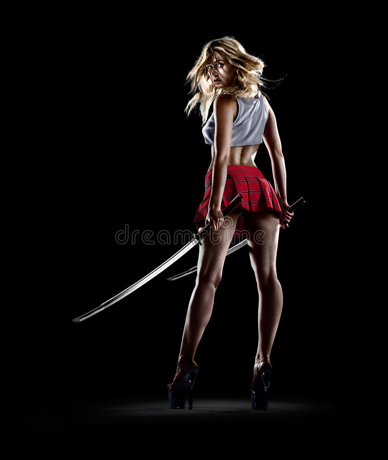 Young girl is standing with the swords stock photography