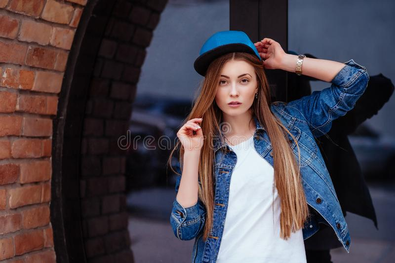 Young sexy glamour woman wearing jeans jacket and baseball cap. Lifestyle city portrait in swag style stock images