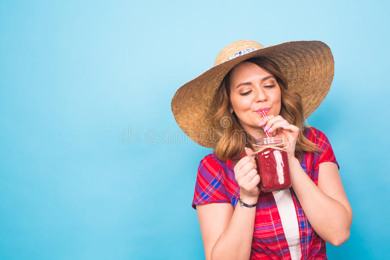 Young woman drinking tasty smoothie on blue background and copy space, vintage outfit, studio lifestyle portrait. Young hipster woman drinking tasty smoothie stock images
