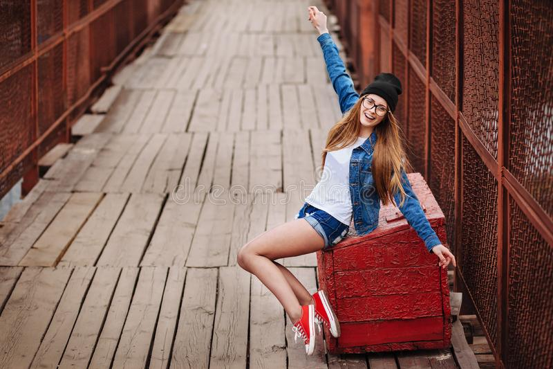 Young sexy hipster woman sitting on red vintage box and laughing. Wearing jeans jacket, hipster black hat and glasses. Lifestyle stock photography