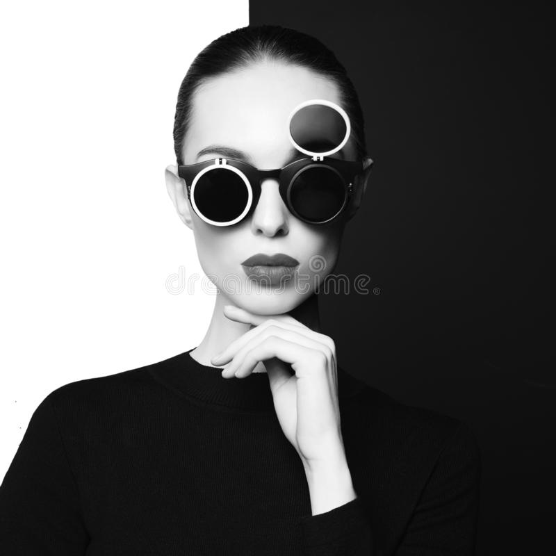 Beautiful young woman with black sunglasses. Young sexy lady with black stylish sunglasses in black-and-white studio. beautiful woman with perfect lips and black stock photos