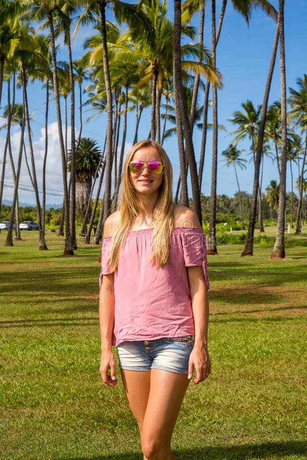 Young lady standing by the palms royalty free stock photos