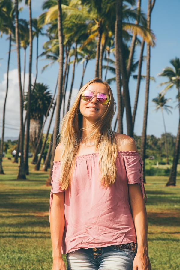 Young lady standing by the palms stock images