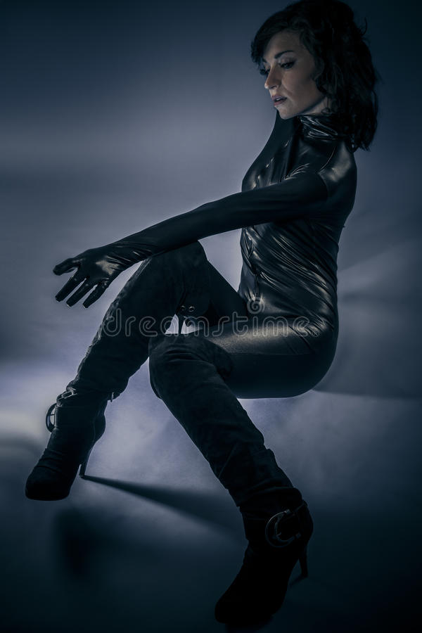 Young latex woman on blue background stock photography