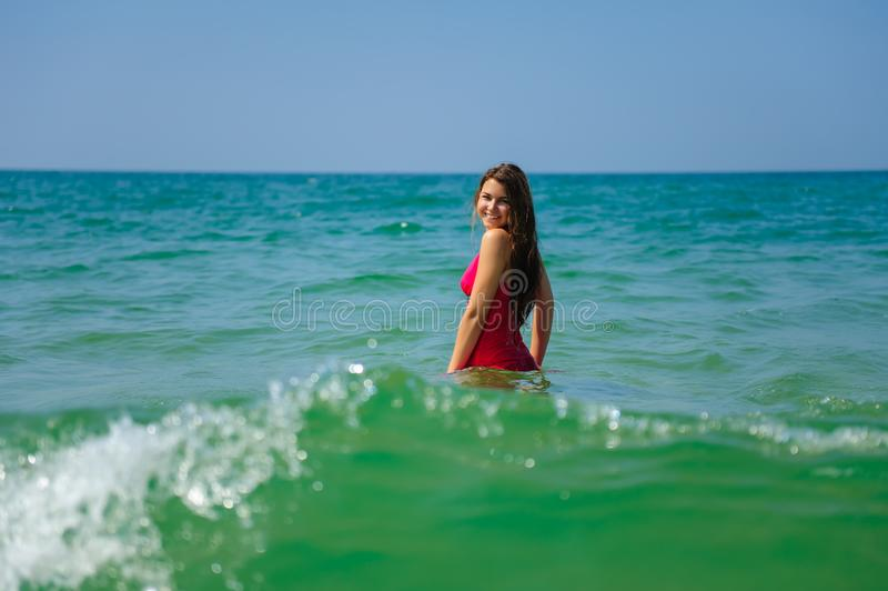Young sexy long haired brunette in red beach dress standing waist-deep in turquoise ocean water on hot day. Beautiful woman posing royalty free stock images