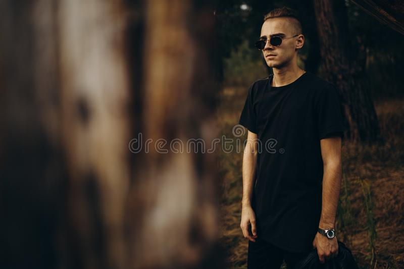 Young sexy man in black shirt and sunglasses standing outdoor in the forest royalty free stock images