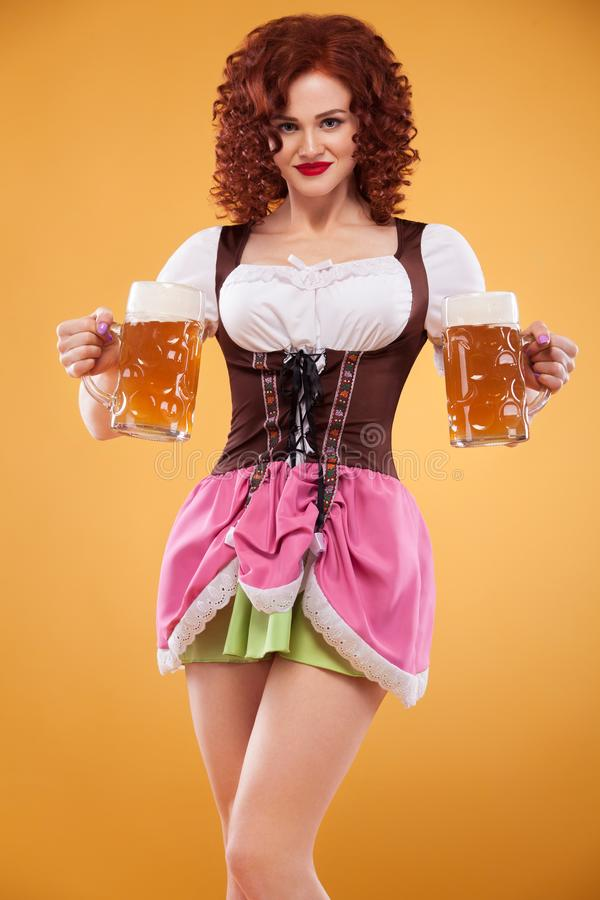 Young Oktoberfest waitress, wearing a traditional Bavarian dress, serving big beer mugs on yellow background. stock photography