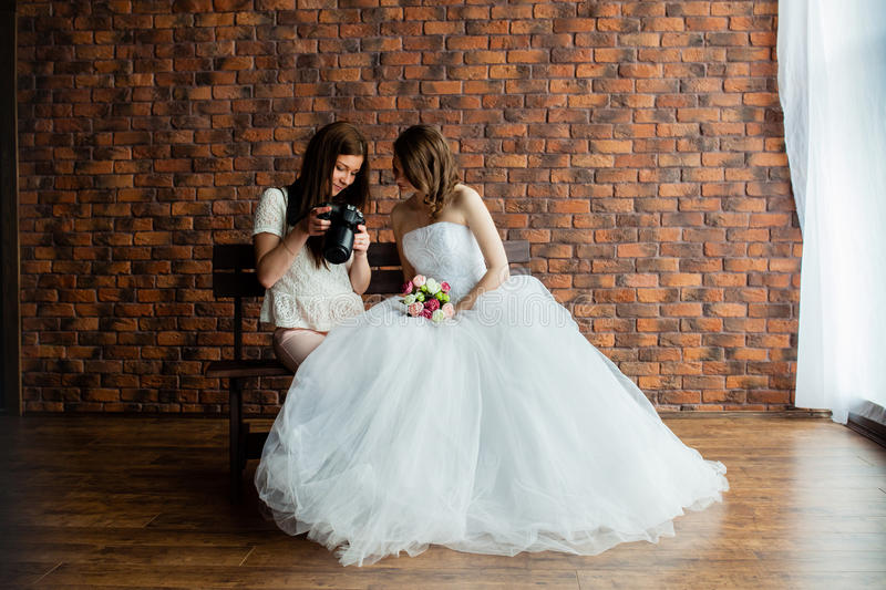 Young photographer shows the bride had just taken photos. Young women photographer shows the bride had just taken photos royalty free stock images