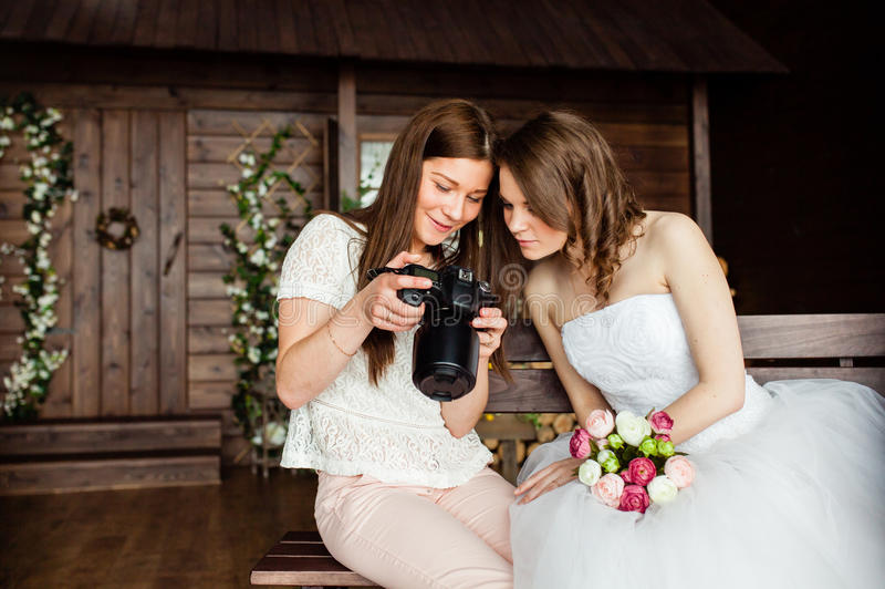 Young photographer shows the bride had just taken photos. Young women photographer shows the bride had just taken photos royalty free stock image