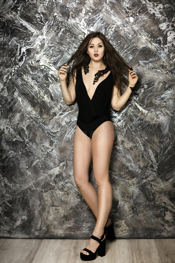 Young and seductive brunette woman with red lipstick in black bodysuit on dark background royalty free stock images