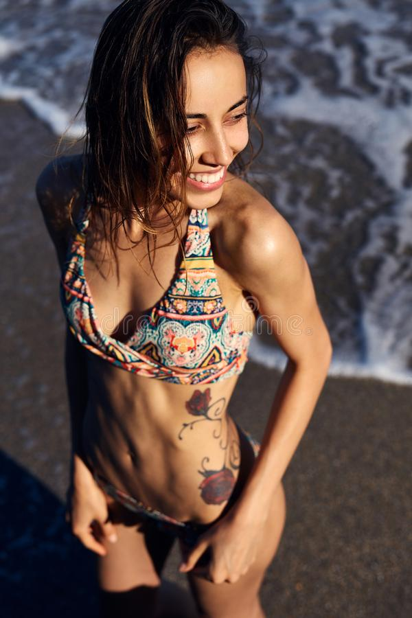 Young skinny woman with tattoo in colored bikini swimwear posing on the. Bitch. Smilling female with fit body. Summer Beach Vacation. Healthy sun tan skin In royalty free stock image