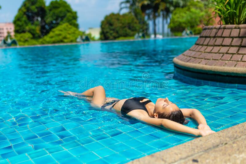 Young sexy slim woman relaxing in tropical swimming pool with crystal blue water in hot summer day.  royalty free stock image