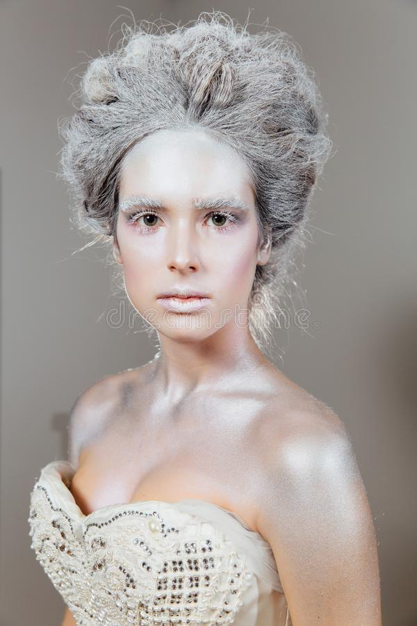 Young snow queen princess. Beautiful snowy hairstyle. Decollete. Fashion. stock photos