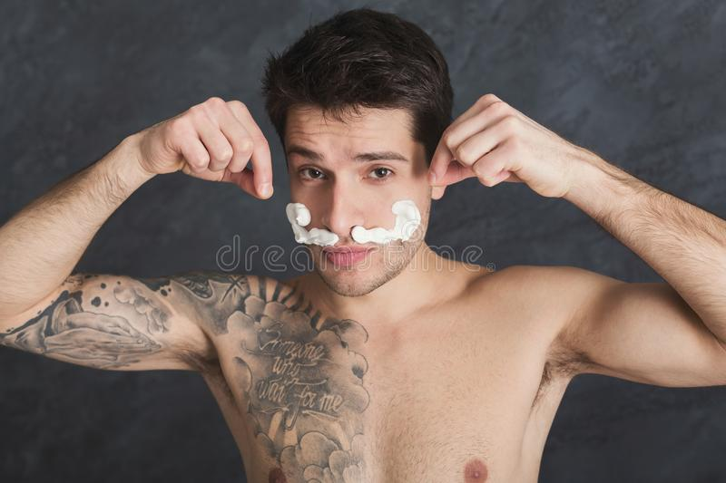 Young tattooed man with moustaches from foam stock photography