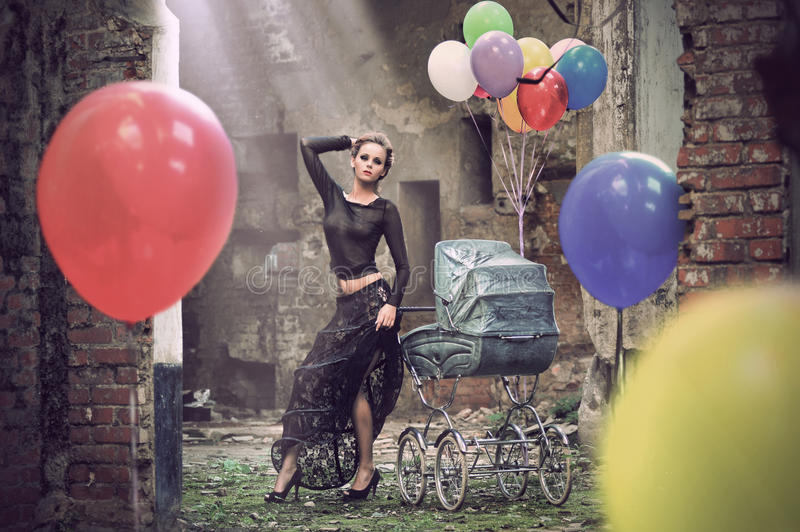 Young woman with balloons and baby carriage royalty free stock photo