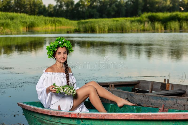 Young woman on boat at sunset. The girl has a flower wreath on her head, relaxing and sailing on river. Fantasy art. Young woman on boat at sunset. The girl has stock image