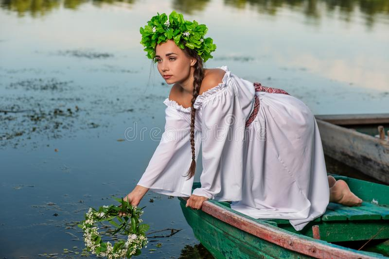 Young woman on boat at sunset. The girl has a flower wreath on her head, relaxing and sailing on river. Fantasy art. Young woman on boat at sunset. The girl has royalty free stock images