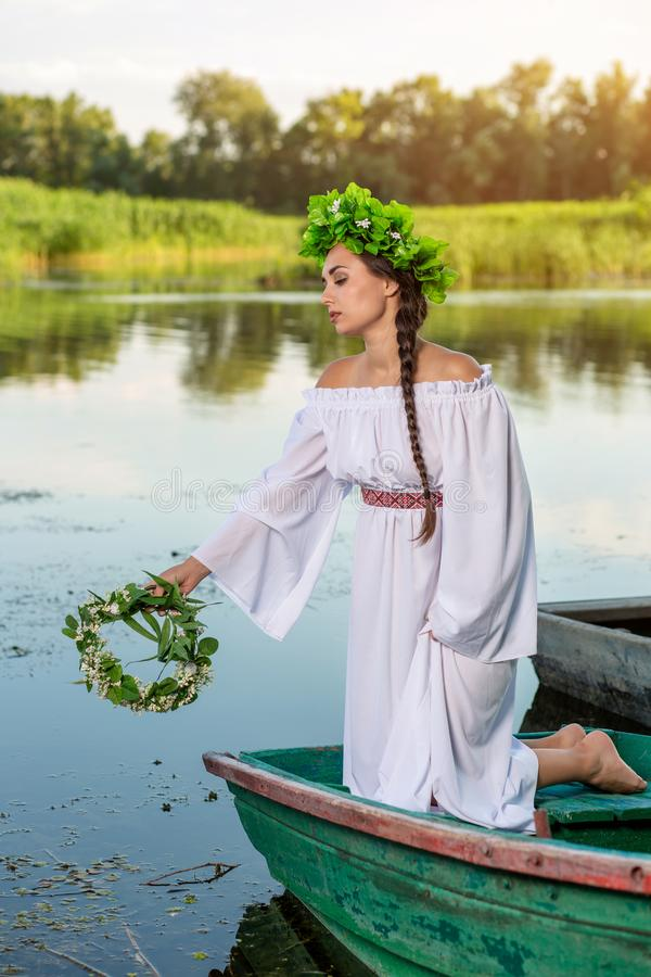 Young woman on boat at sunset. The girl has a flower wreath on her head, relaxing and sailing on river. Fantasy art. Young woman on boat at sunset. The girl has royalty free stock photography