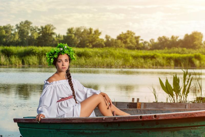 Young woman on boat at sunset. The girl has a flower wreath on her head, relaxing and sailing on river. Fantasy art. Young woman on boat at sunset. The girl has royalty free stock image