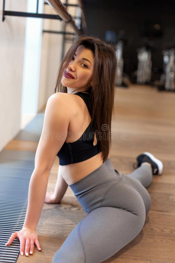 Young sexy woman doing stretching exercises in gym stock photos