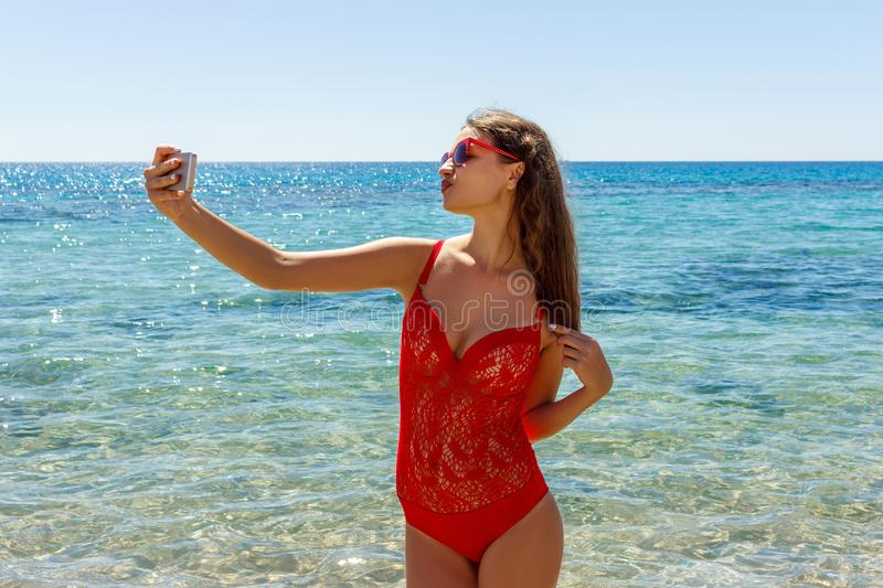 Young woman dressed in fashion swimsuit using mobile phone camera for take selfie stock photos