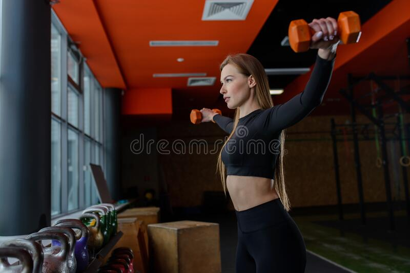 Young sexy woman during fitness workout at gym. Exercises with dumbbells. Lateral raise hands. stock photos