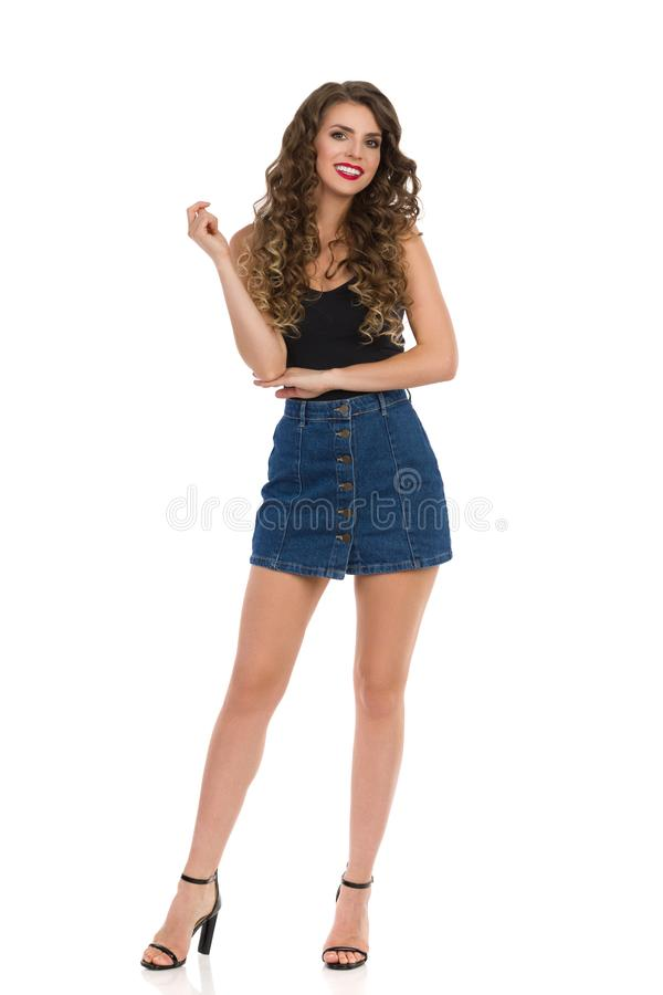 Young Sexy Woman In Jeans Mini Skirt, Black Top And High Heels. Confident sexy young woman in jeans mini skirt, black top and high heels is standing, looking at stock photo