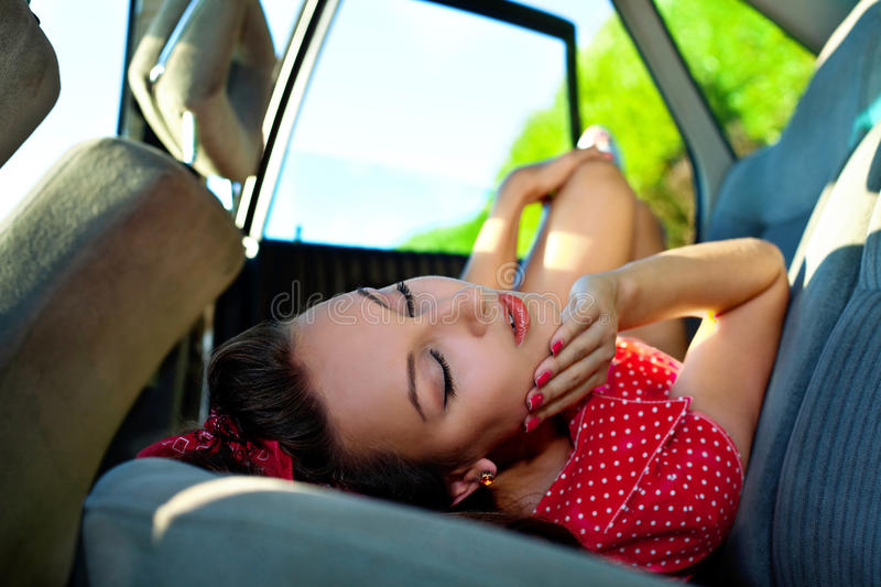 Young woman lay in car - pinup style stock photography