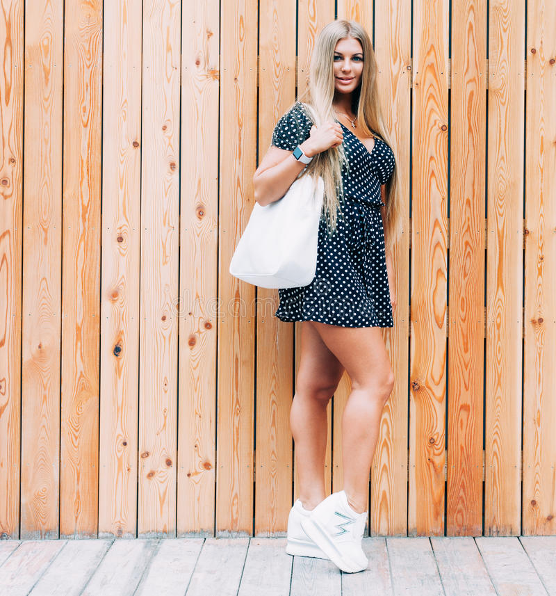 Young woman outdoor posing in summer. Fashion swag dressed in short dress and Fashion sneakers, on shoulder white big handbag royalty free stock photos