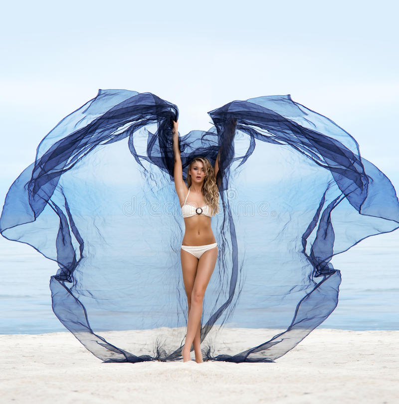 Young and woman posin on the beach in blue silk. Young, fit and beautiful woman on the beach dancing with a blowing silk royalty free stock image