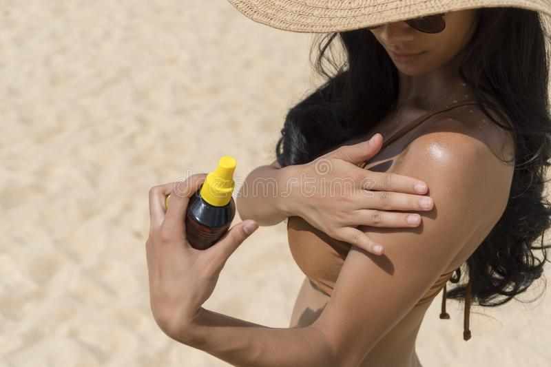 Young sexy woman putting tanning oil on her arm, hand holding sunscreen suntan lotion spray skin care product at the beach, summer stock photo