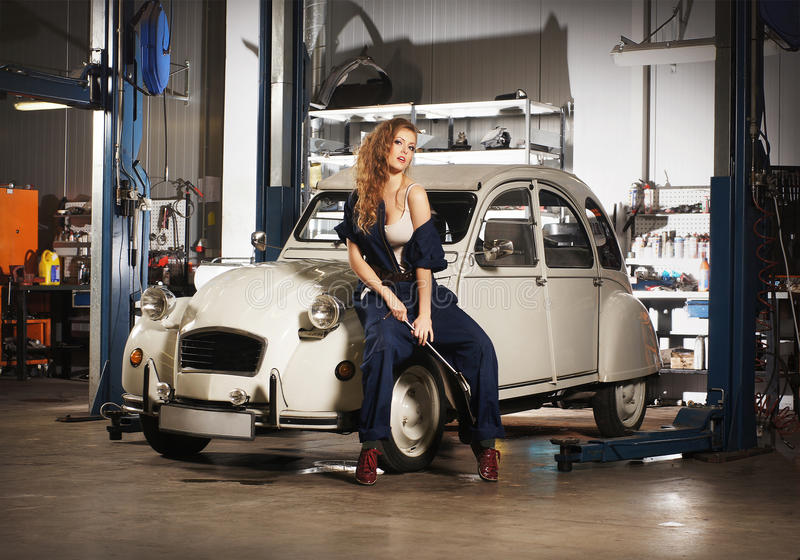 Young woman repairing a retro car stock images
