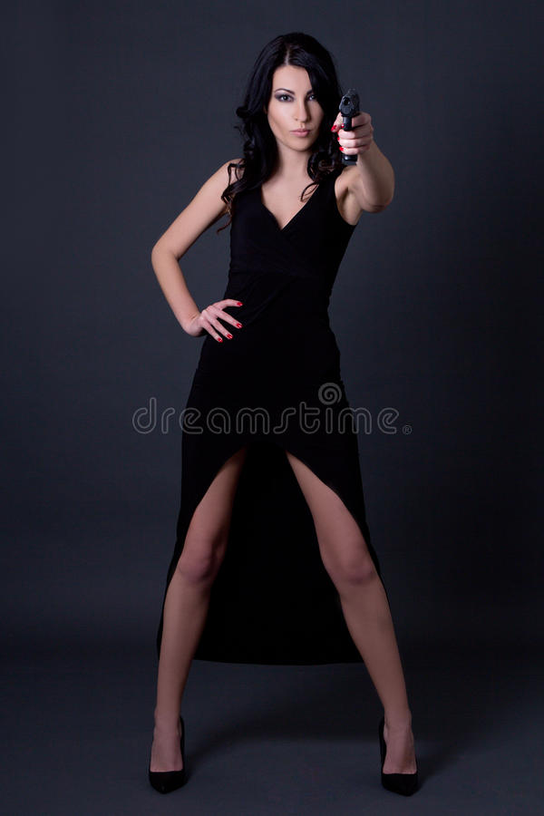 Young woman secret agent in black dress posing with gun ove stock images