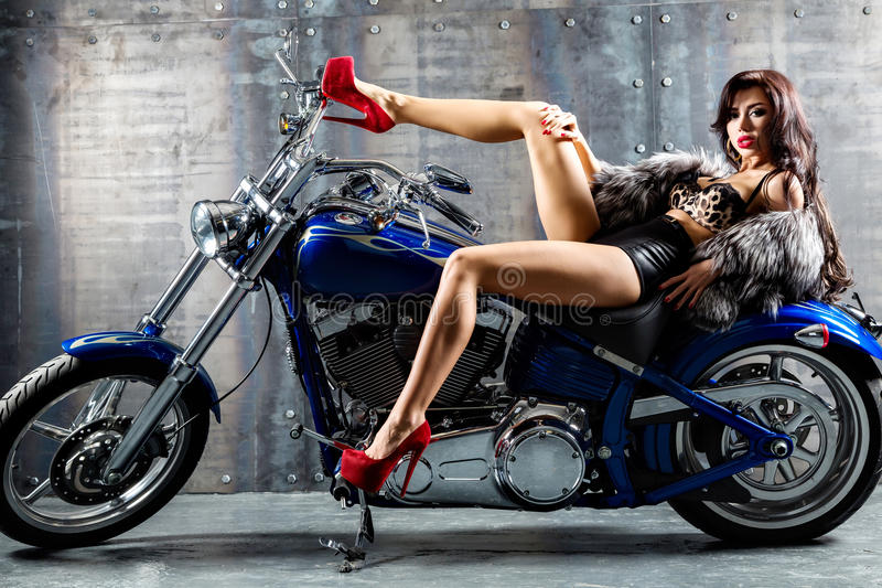 Young woman sitting on motorcycle. Attractive girl on a motorbike in a studio stock images