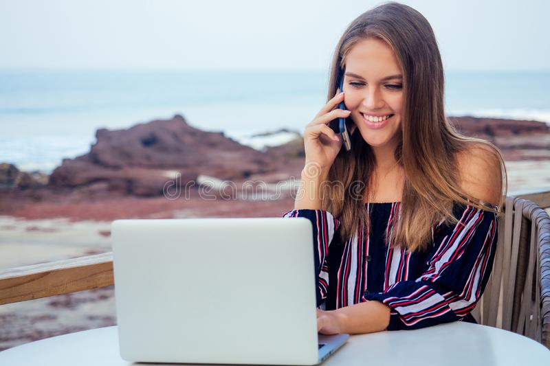 Young sexy woman in a stylish striped jumpsuit using laptop and telephone freelancing on the tropical paradise beach stock photos