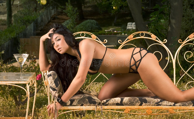 Young woman in swimsuit crawling on bench stock photography