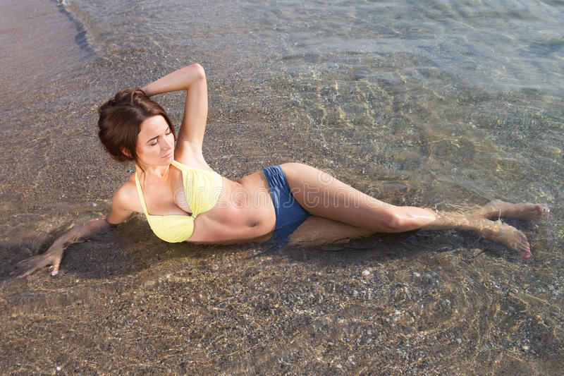 Young woman in a swimsuit in the sea water royalty free stock images